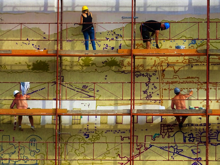 workers standing on a scaffolding