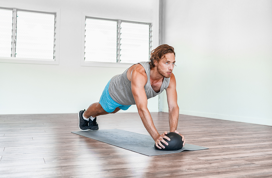 Man working out at home with a medicine ball and a yoga mat