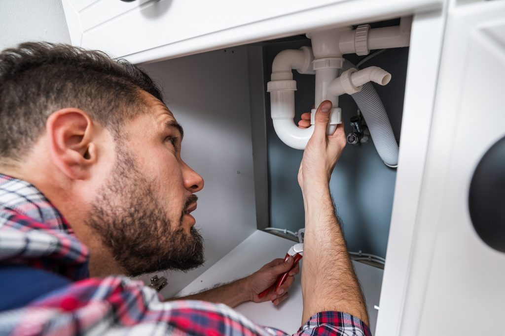 Reliable plumber in Lower Hutt fixing the sink pipe